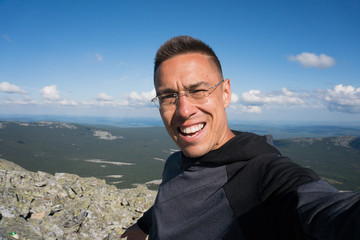 a man takes pictures at the top of a mountain