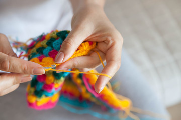 A woman knits a colored cloth. Hands close-up.