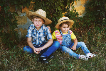 Brother and sister sitting on the grass in straw hats in a stone wall