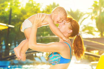 Mother holding over head and kissing a laughing child at tropical summer swimming pool background.