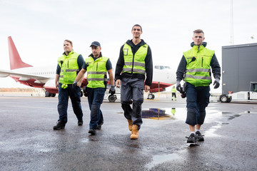 Full Length Of Workers Walking On Wet Runway