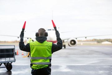 Ground Crew Signaling To Airplane