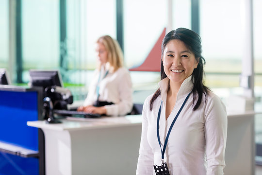 Ground Staff Smiling While Colleague Working At Airport Receptio