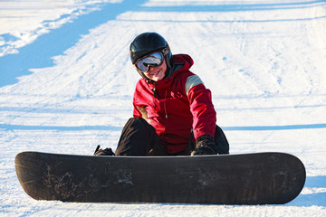 Female snowboard sportswoman resting on the snow slope