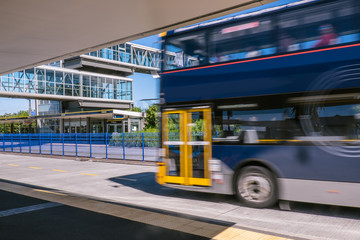 Blurred moving bus at park and ride transport station on North Shore, New Zealand, NZ
