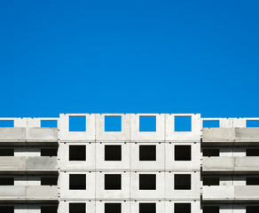 Fragment of a building under construction against a blue sky.