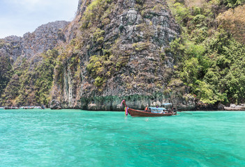 longtail boat moored floating at Pileh bay is blue lagoon with limestone rock at phi phi island in the andaman sea Krabi,Thailand.
