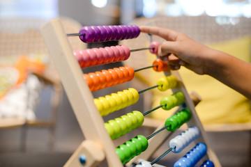 Close up on colorful abacus playful activity, educational interior background. Happy joyful developmental lifestyle
