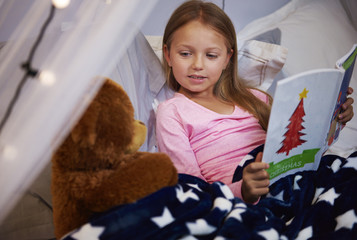 Girl reading storybook with her a teddy bear