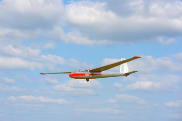 Glider flying on a blue sky background