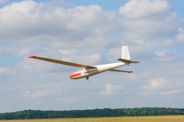 Glider flying on a blue sky background