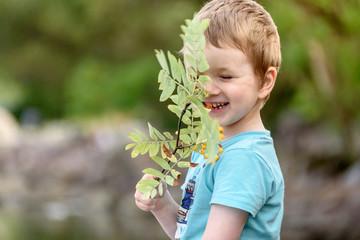portrait of a laughing little boy in nature. Summer portrait