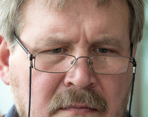 Portrait of a man with a mustache in glasses. Close-up. Macro