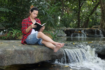 Portrait of young hipster man in red shirt reading a book in beautiful nature background.
