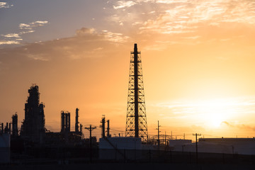 Silhouette oil refinery at sunrise. Oil factory, petrochemical plant tower, gas flare, smoke stacks and machinery in Corpus Christi, Texas, USA. Petroleum industry background.