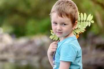 portrait of a serious little boy in nature. Summer portrait