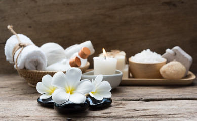 Spa wellness concept,white candle,milk soap,salt,towel,flowers and herbal massage ball on rustic...