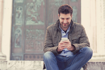 Man texting on phone. Casual urban guy using smartphone smiling happy outside old town building.