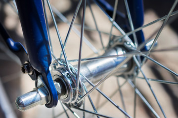 macro detail of a metal hub of a bike with blue forks