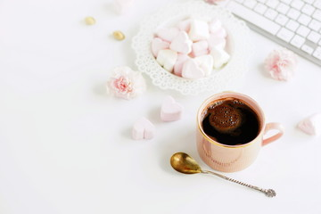 Flat lay, top view office table desk. Feminine workspace with laptop, pink cup of coffee and pink marshmallows hearts on white background.Copy space