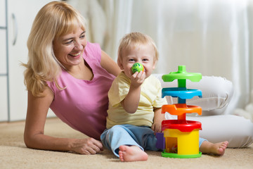 Mom and her child with colorful logical toy. Family having a fun playing together at home.