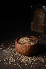 Brown, red and black rice mixed in a clay bowl on a grange concrete dark black background. Dark and moody image. Close up