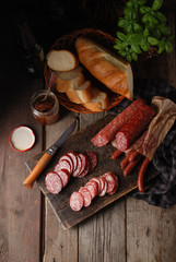 Various varieties of sausage on a cutting vintage board, fresh bread baguette, dried tomatoes, fresh green basil and beer on a rustic wooden gray background. Top view