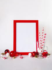 Mock up red frame on a white background with Christmas decorations and candys. Place for text, Invitation, greeting card, paper.
