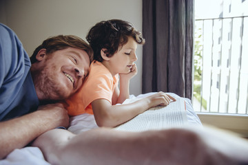 Son reading to his father on bed