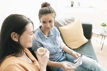 Mother and adult daughter sitting on couch at home looking at photos