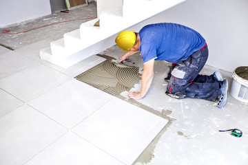 Tile laying tiles at home. Construction worker laid floor tiles.