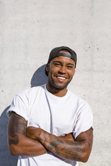 Portrait of laughing young man with arms crossed standing in front of concrete wall