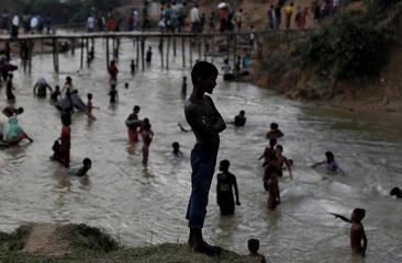 Rohingya refugees swim in a river running through a camp in Cox's Bazar, Bangladesh