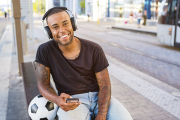 Portrait of smiling young man with soccer ball, headphones and cell phone waiting at tram stop
