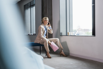 Smiling businesswoman on the phone sitting at the window