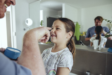 Father putting facial cream on daughter's face