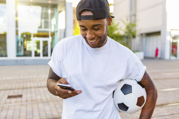 Laughing young man with soccer ball looking at cell phone