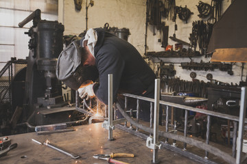 A blacksmith wears safety gear and is welding a metal construction in a metalsmith's workshop.