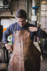 A blacksmith puts on a leather apron in a workshop.