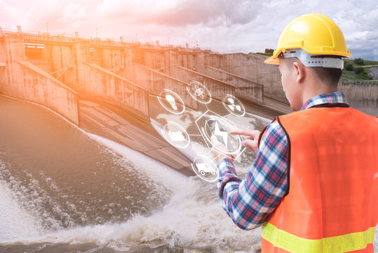The abstract image of the engineer holding smartphone with hologram and the hydroelectric dam is backdrop. the concept of clean energy, hydroelectricity, water management and engineering.