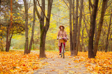 travel concept young woman with bicycle picnic set in bright autumn city park