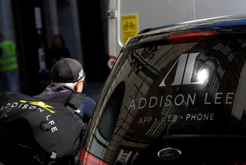 An Addison Lee courier pedals past an Addison Lee minicab in central London