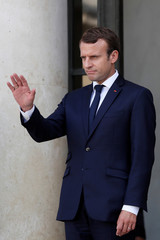 French President Emmanuel Macron waves as a guest leaves the Elysee Palace in Paris