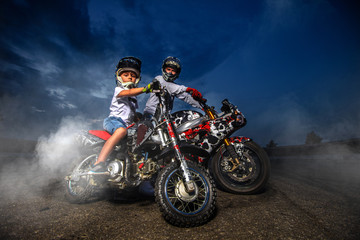 Father and son motorcycle bikers. Bikers family dressed in protective suit and helmet. Wall mural