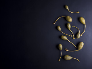 Italian caper berries with stems in small bowl isolated on black background