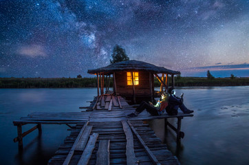 Boy and girl seatting near wooden house on the lake with lightning window in night at the stars night sky background.