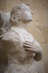 A statue of a woman with crossed arms is an architectural detail in the Baroque style near the temple wall. Lecce, Italy.