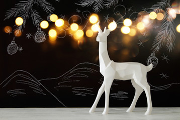 White reindeer on wooden table over chalkboard background whith hand drawn chalk illustrations.