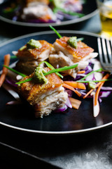 Closeup of a plate of gourmet pork belly with Asian style slaw.