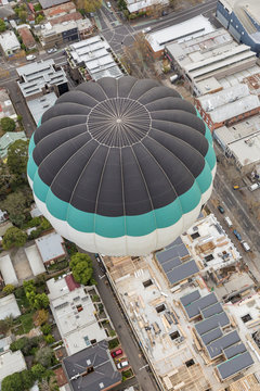 Black, green and white hot air balloon floating above suburban streets shot from above